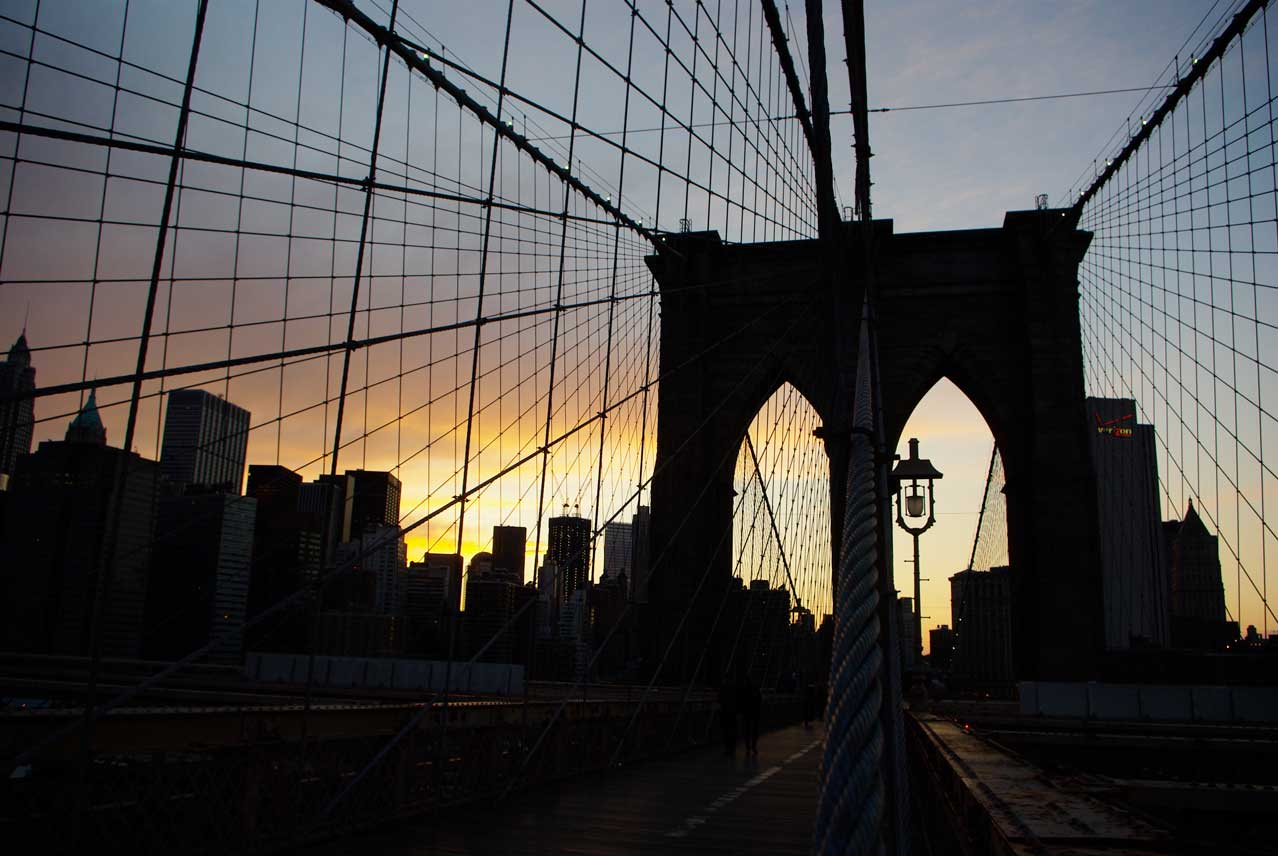 Sunset through the towers of the Brooklyn Bridge