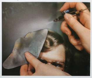 Airbrushing with a hand-held mask.