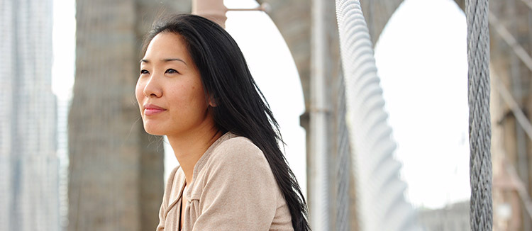 Photograph of poet Tina Chang with Brooklyn Bridge in the background