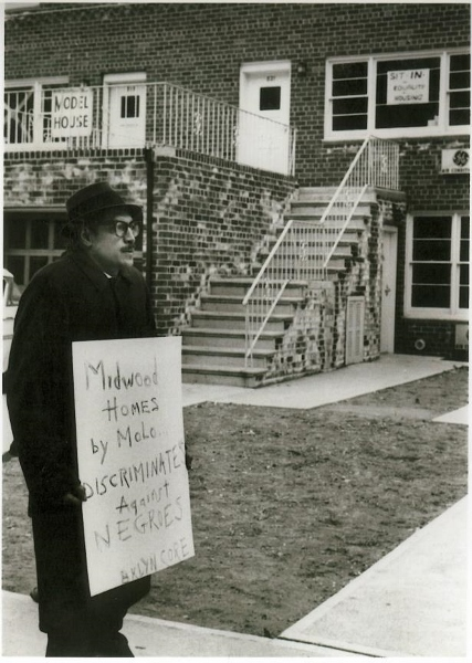 "Photograph of CORE member picketing outside a home with sign reading ""Midwood Homes by MOLO discriminates against negroes -- BKLYN CORE"""