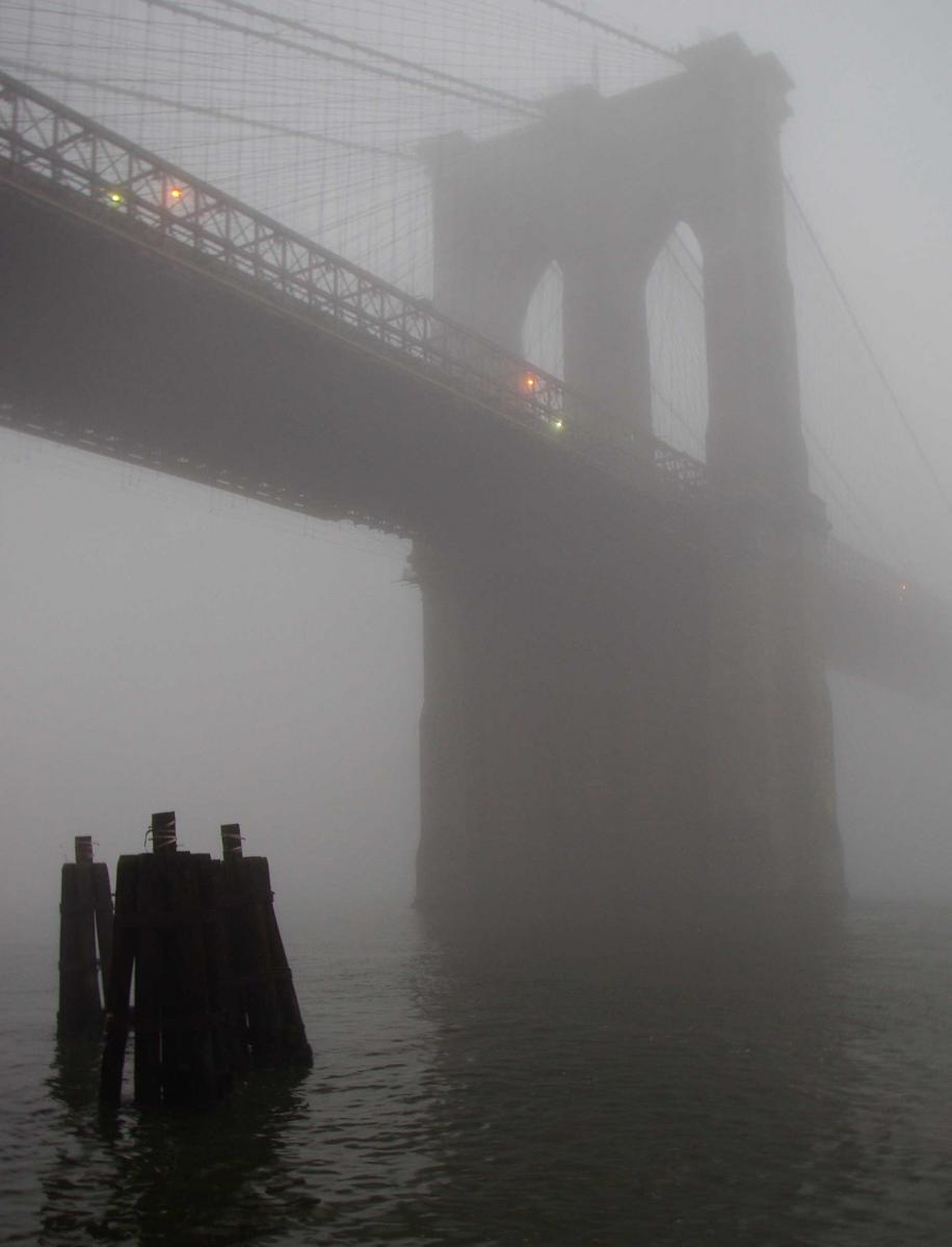 Brooklyn Bridge in fog with three pylons in foreground