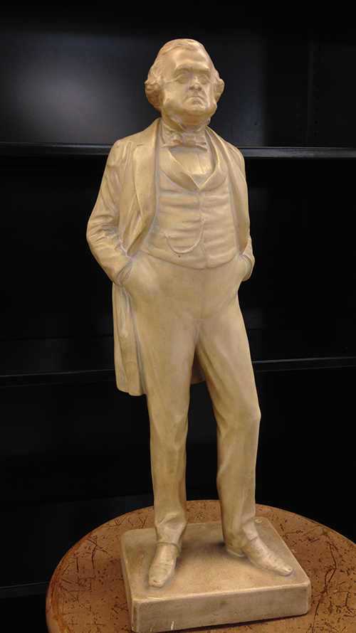 Plaster statue of man in 19th century dress.
