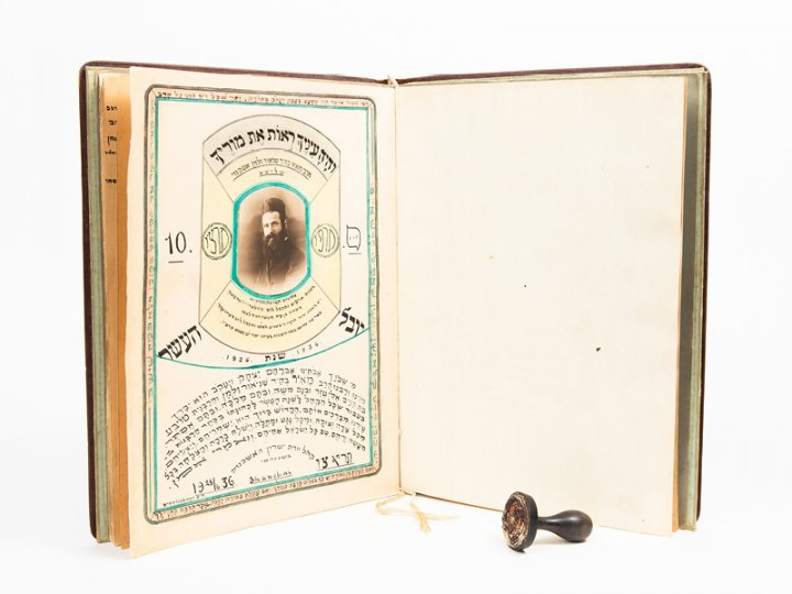 Marking stamp of Rabbi Meir Ashkenazi and handmade album presented to Rabbi Ashkenazi. Stamp is courtesy of Miriam Pogrow and notebook is courtesy of the Wilshanski family, shown here courtesy of Amud Aish Memorial Museum