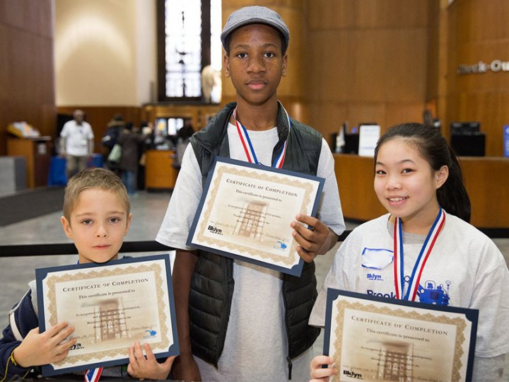 Students receive their certificate of completion at the BKLYN Robotics League Competition