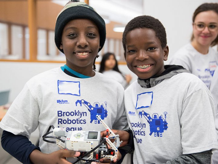 Two participants in the BKLYN Robotics League show off their robot.