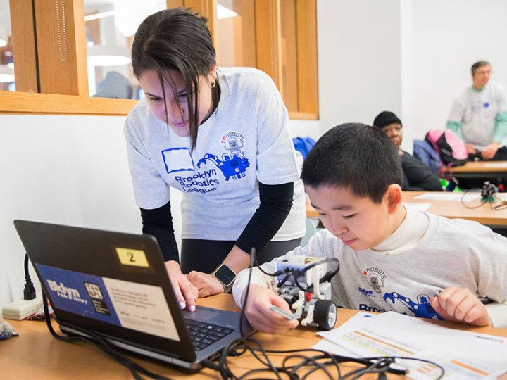Two competitors in the BKLYN Robotics League research their robot.