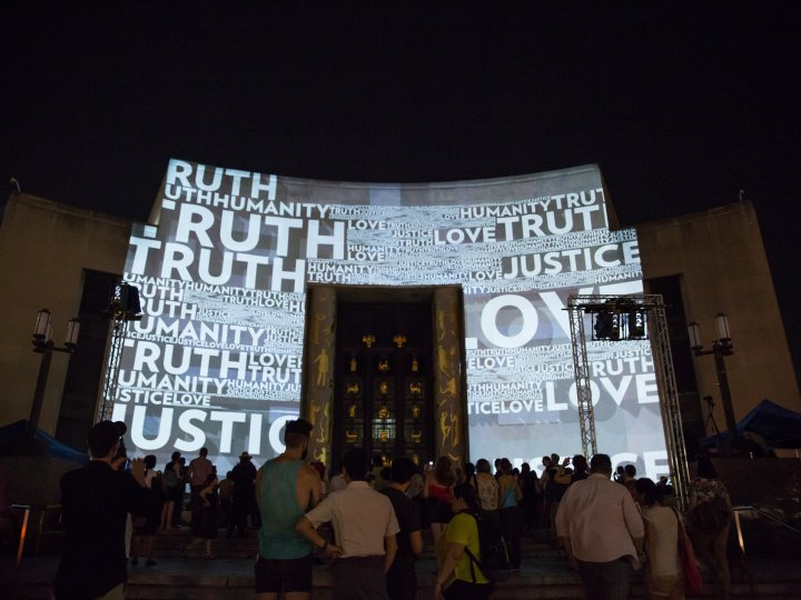 A photo of the Central Library during its Brooklyn Gaze event - with text projected onto the facade
