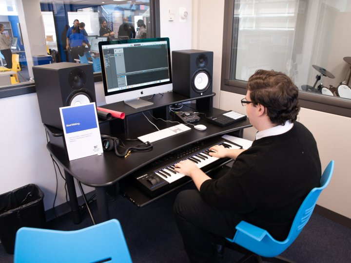 A teenage boy uses a keyboard and recording equipment to make a song at the Teen Tech Center.