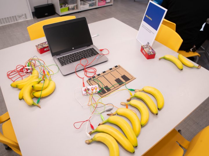 A table filled with 10 bananas that are hooked up to wires. The bananas are being used in an experiment to power a game controller at the Teen Tech Center