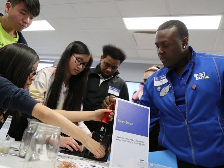 Four teenagers gather around a table as an adult demonstrates a task at the Maker Station at the Teen Tech Center.