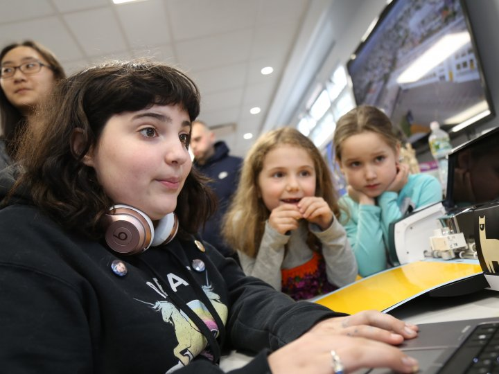 A teen girl with dark hair plays a game on a laptop while two younger girls look on.