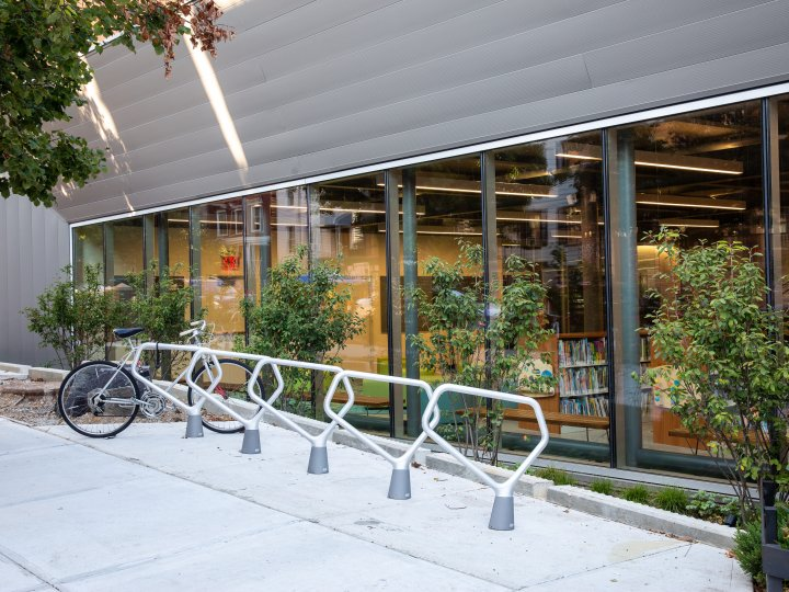 Bike rack outside Greenpoint Library, with windows looking into the space directly behind bike racks