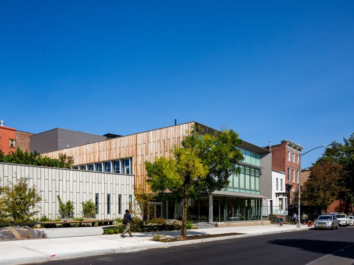 Side view of Greenpoint Library, with wood-paneled facade and roof garden in view