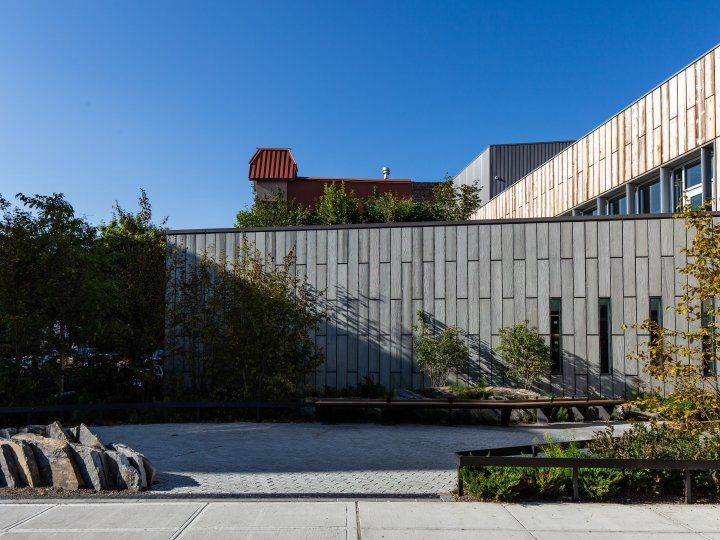 Front view of Greenpoint Library's garden, with granite rock outcropping and  bioswale and benches