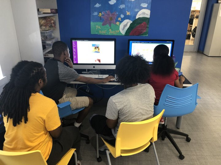 A group of teens learn how to use micro:bits to create and connect to Scratch programs.