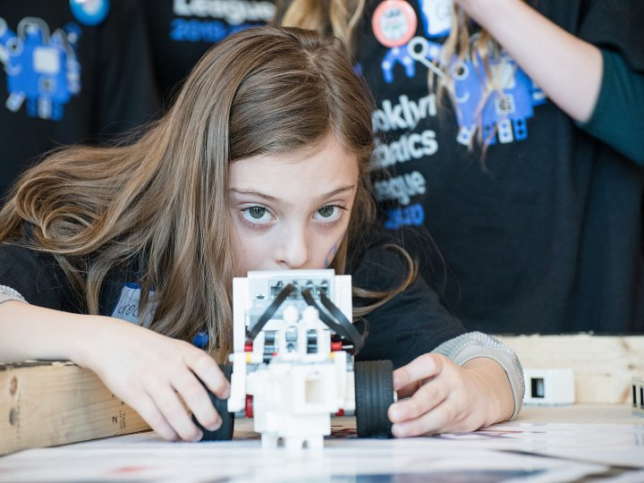 A pre-teen girl looks directly at the camera as she aims her robot down the course.