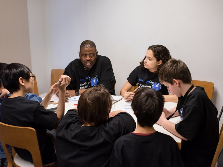 Five pre-teens that are part of a LEGO robot team circle a table while an adult talks to them about their robot.