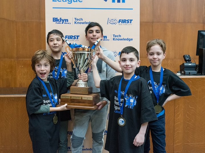 Five pre-teen boys lift up a trophy.