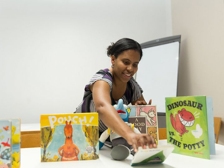 A woman leans over books set up on a table as she sets up for a televisit.