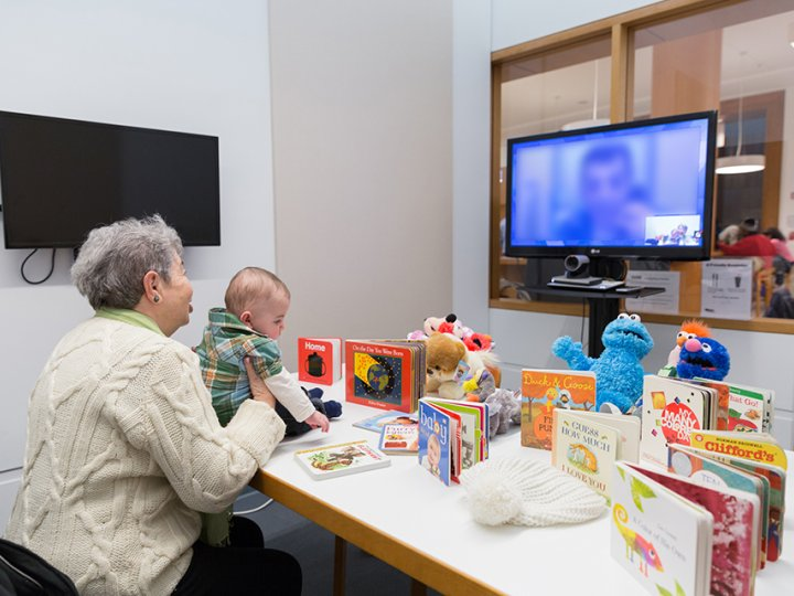 An older woman sits at a table with books and a baby on the table while they have a video chat with a man on a Television screen whose face is blurred.