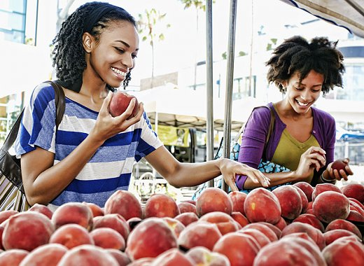 Two women shopping for peaches at a greenmarket stand