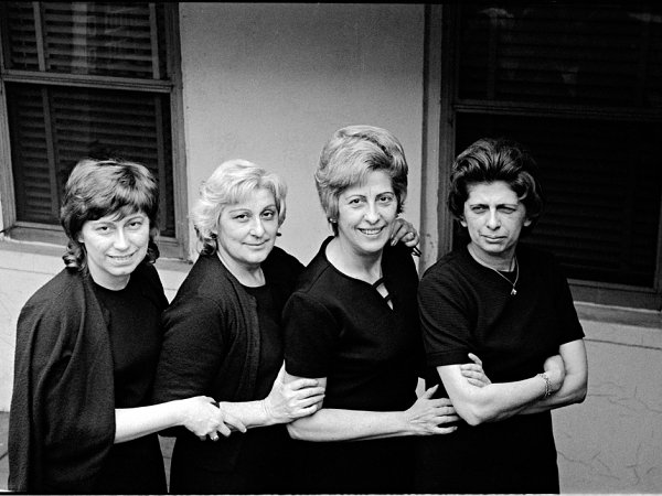 4 women dressed in black standing next to each other.
